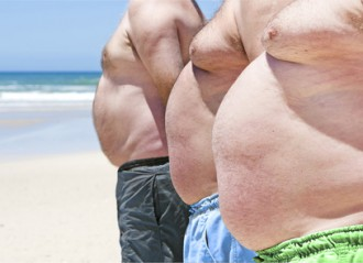 Close up of three obesely fat men on the beach showing their unhealthy bellies